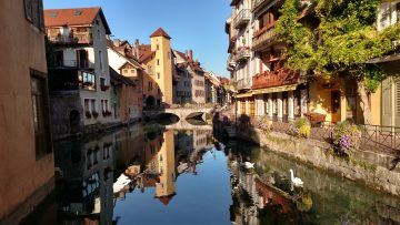 A view of Annecy old city overlooking a stone bridge and canal