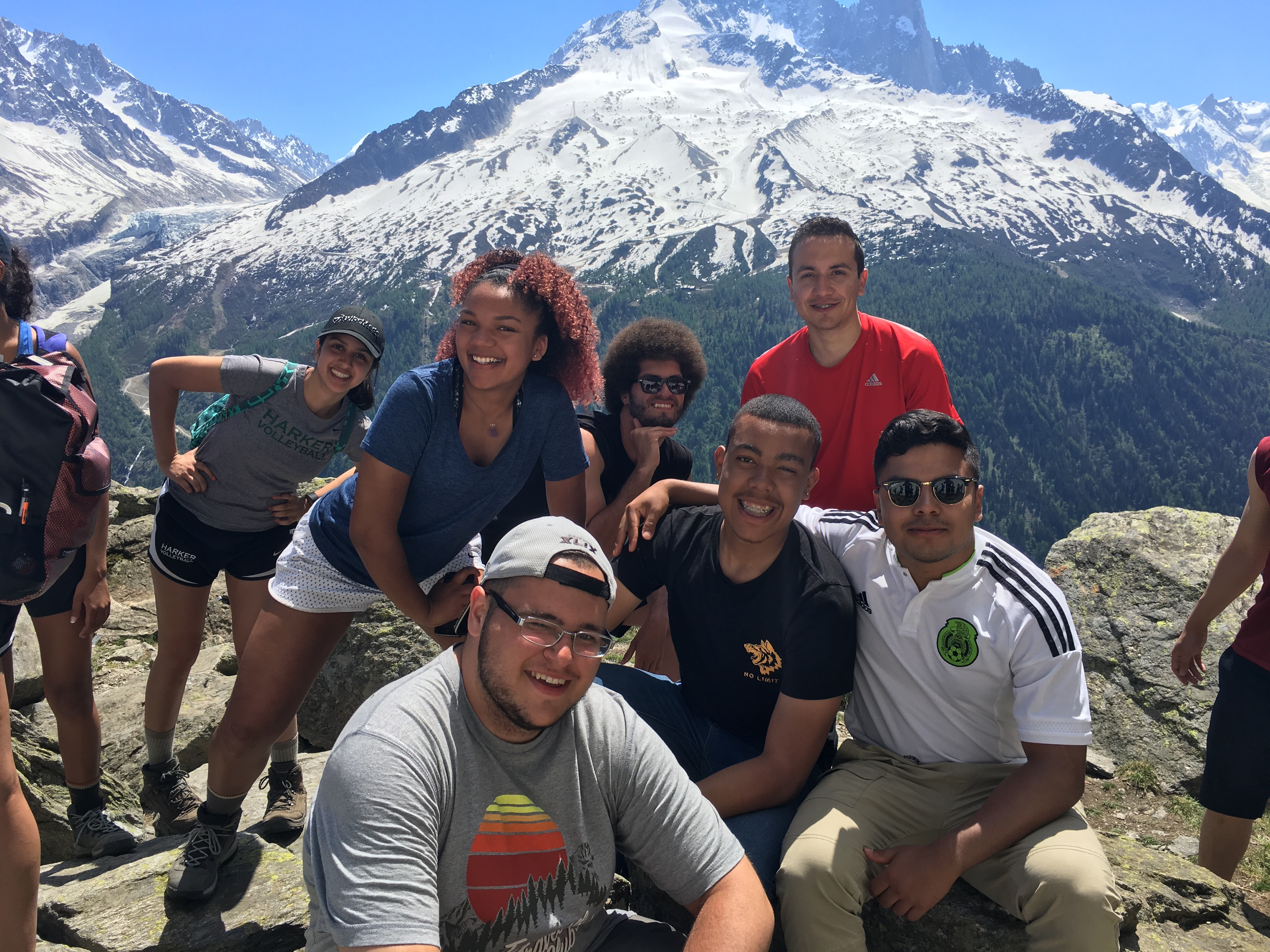 Against the backdrop of a snow-capped mountain, students face the camera and smile