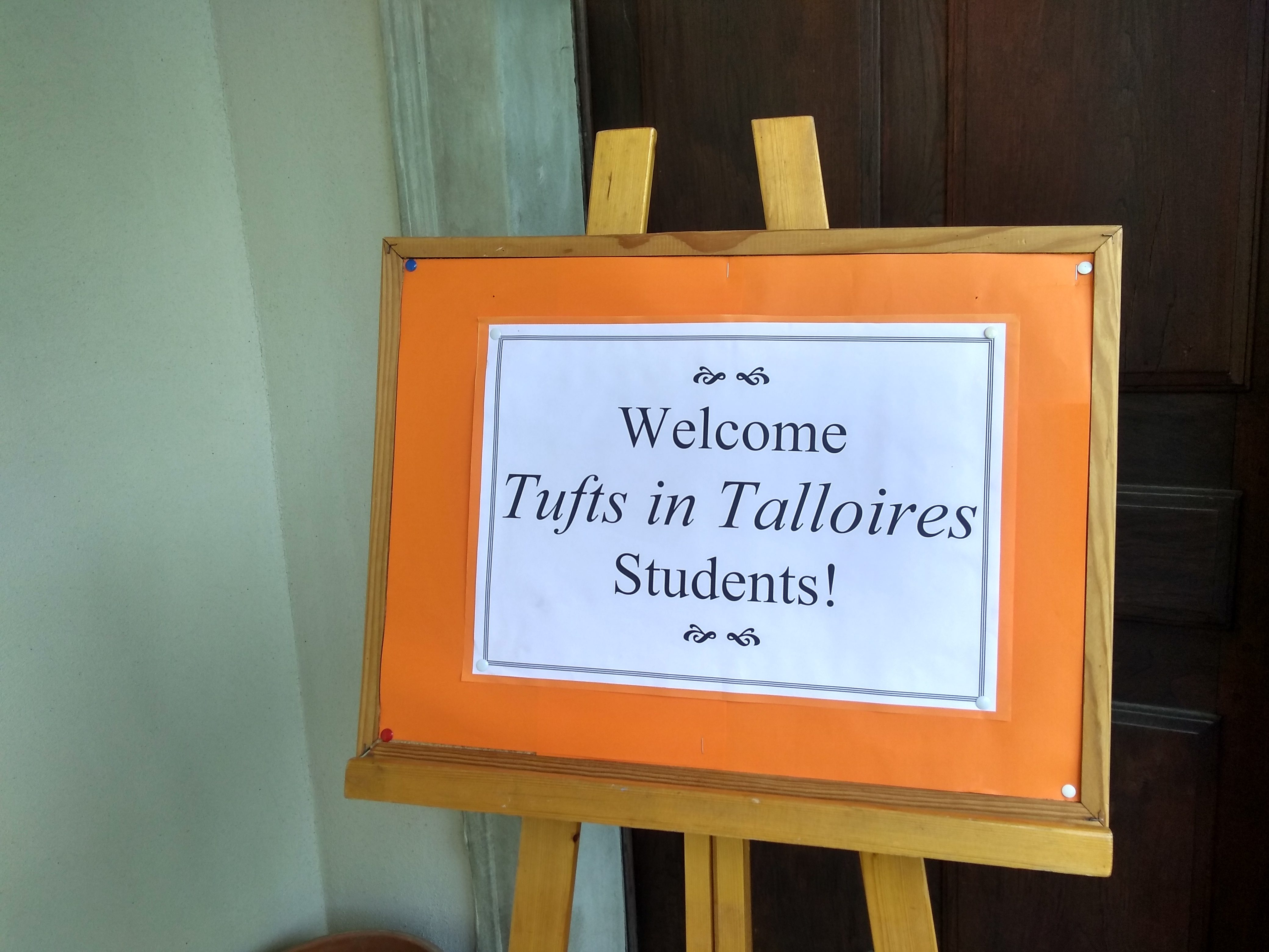 """An orange bulletin board reads """"Welcome Tufts in Talloires students!"""""""