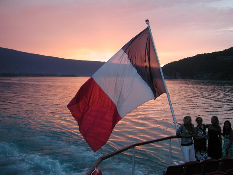 The French flag waving off the back of a boat on Lake Annecy