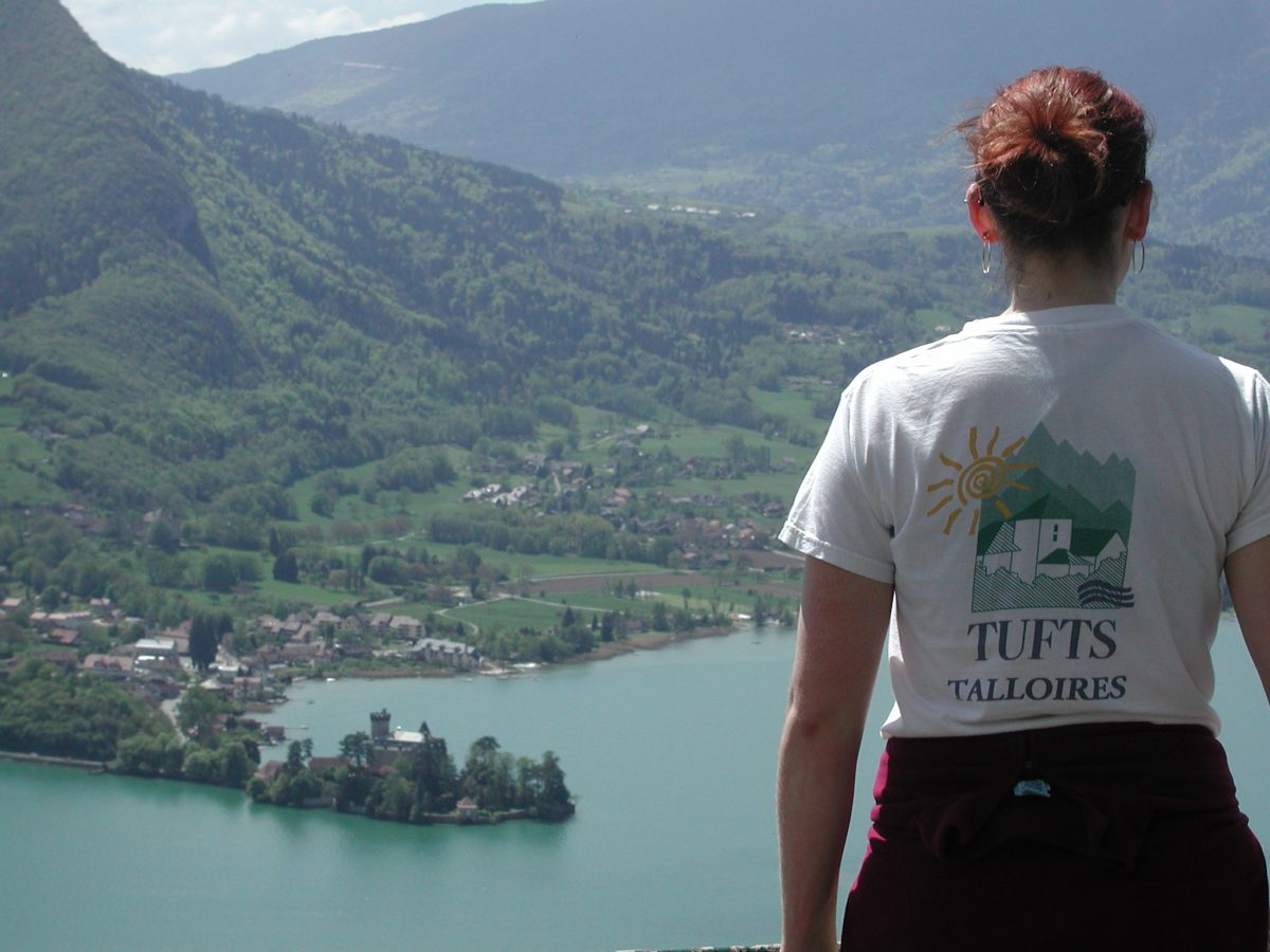 Student wearing a Tufts Talloires t-shirt overlooking Lake Annecy