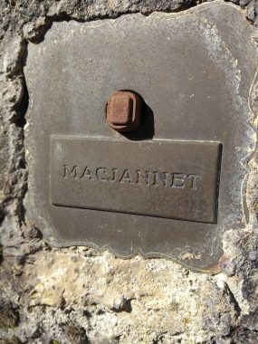 """An old doorbell, now rusted, with the word """"MacJannet"""" above it in stone"""