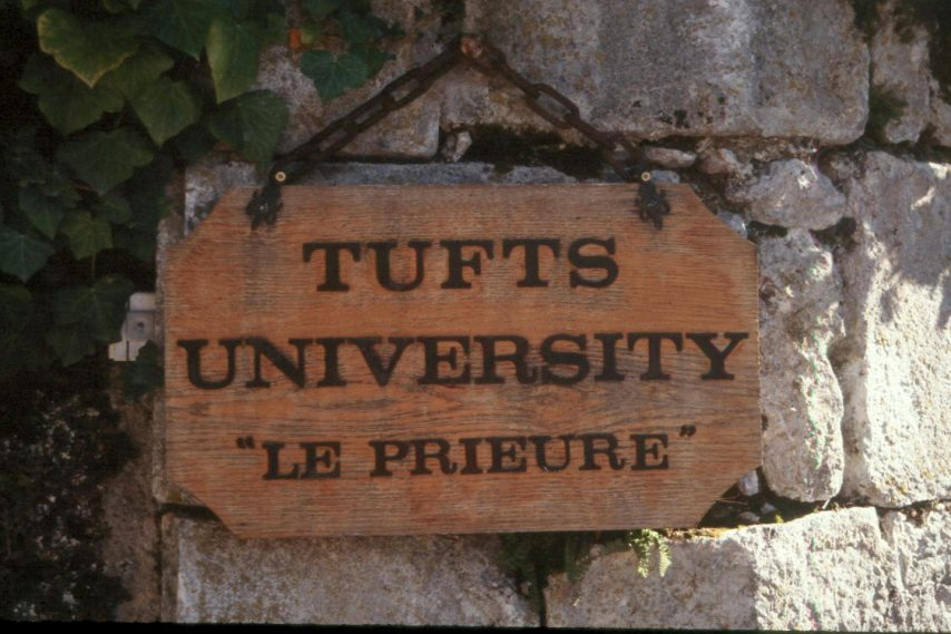 """A wooden sign stating """"Tufts University - Le Prieure"""""""