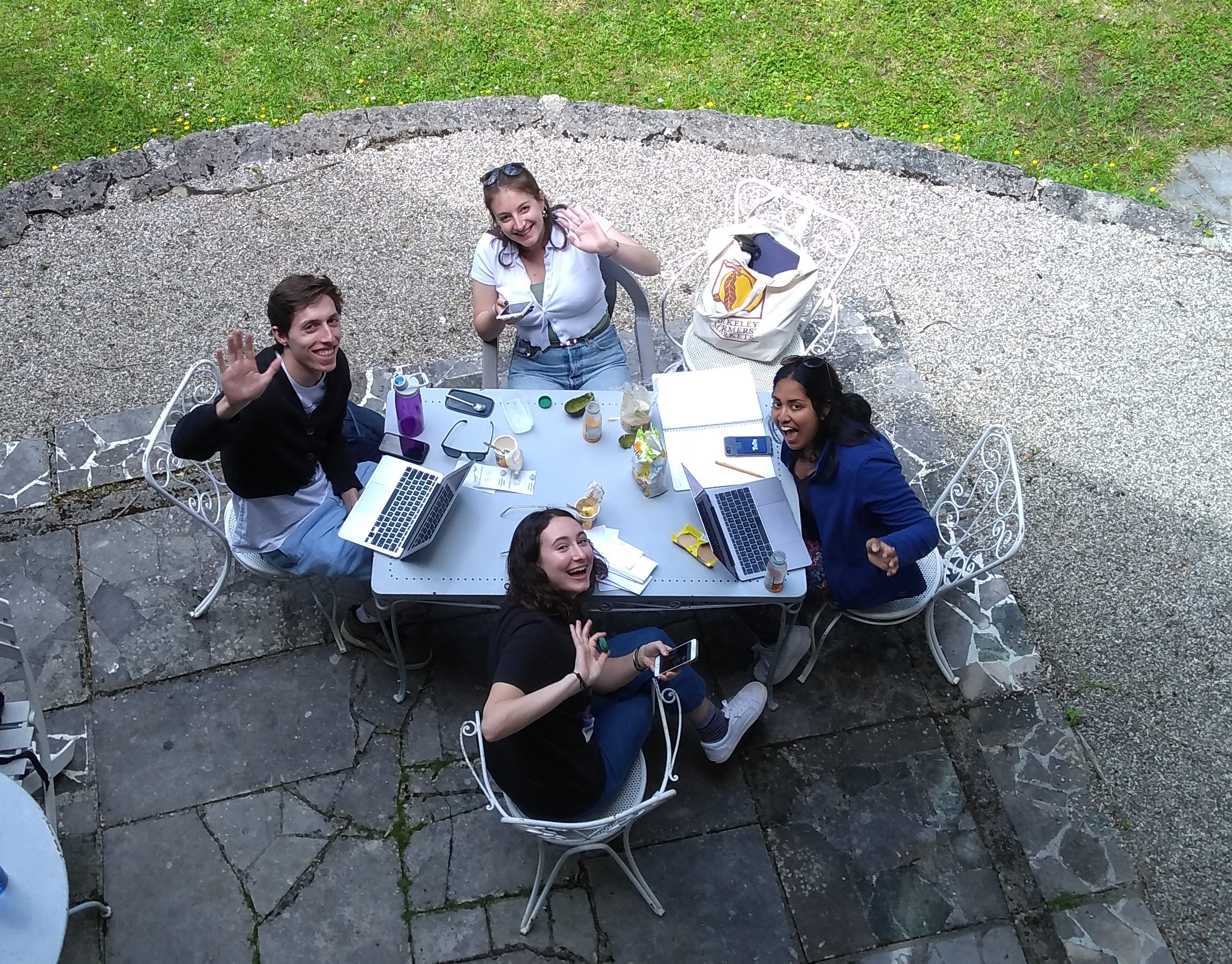 An aerial view of four students sitting at a table in the garden and waving