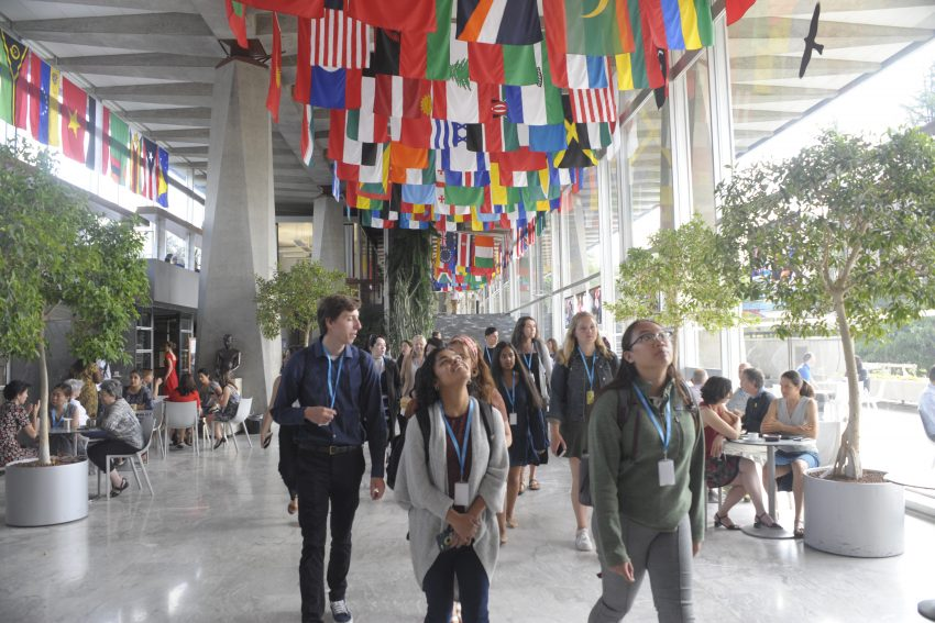 Students looking up at a ceiling of many nations' flags