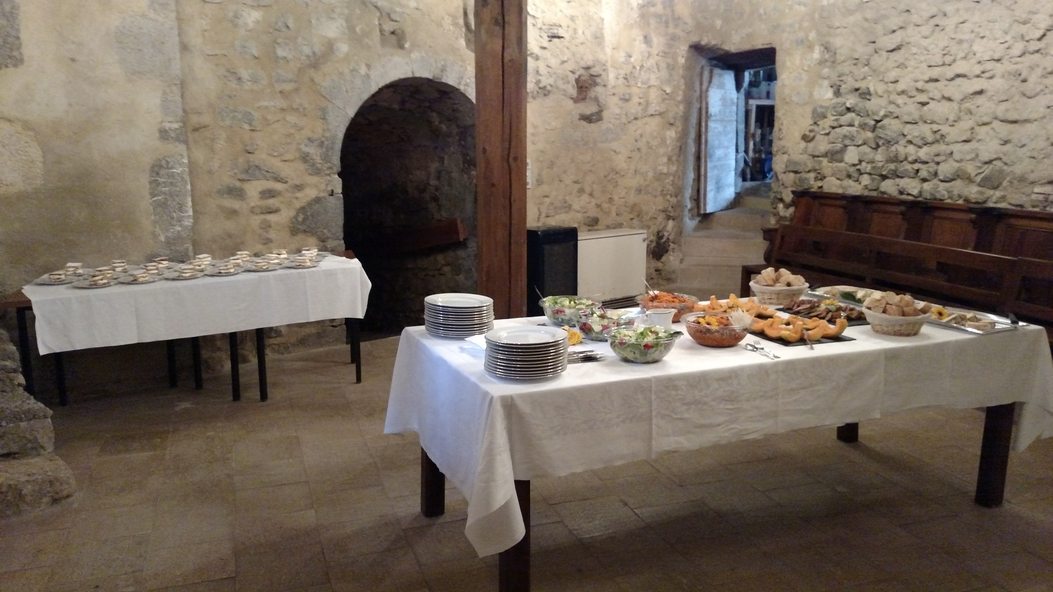 Tables with a buffet meal set up in an old room of the Priory