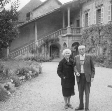 A black-and-white portrait of the MacJannets in front of the Priory.